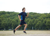 Profile of a young man jogging outdoors — Stock Photo