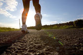 Woman running on road in sneakers — Stock Photo
