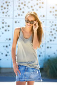 Beautiful young woman smiling with sunglasses — Stock Photo