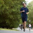 Young man taking casual jog in city park — Stock Photo #50448101