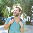 Happy young man traveling with backpack — Stockfoto