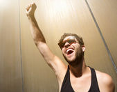 Cheerful young man posing with arm raised  — Stock Photo