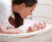 Attractive woman with baby in cot — Stock Photo