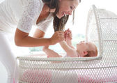 Smiling woman holding baby in cot — Stock Photo