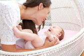 Young woman smiling with newborn infant — Stock Photo
