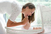 Attractive mother playing with baby in cot — Stock Photo