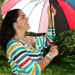 Beautiful young girl posing on nature with color umbrella — Stock Photo