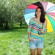 Beautiful young girl posing on nature with color umbrella — Stock Photo #12224923