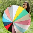Beautiful young girl posing on nature with color umbrella — Stock Photo #12224928