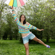 Beautiful young girl posing on nature with color umbrella — Stock Photo #12224944