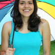 Beautiful young girl posing on nature with color umbrella — Stock Photo #12224948