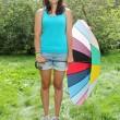 Beautiful young girl posing on nature with color umbrella — Stock Photo #12224951