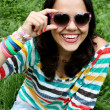 Beautiful young girl in sunglasses sitting on the grass — Stock Photo