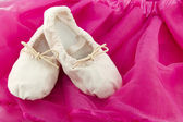Ballet shoes of a girl on pink background — Stock Photo