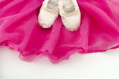 Ballet shoes of a girl on a pink ballet skirt — Stock Photo