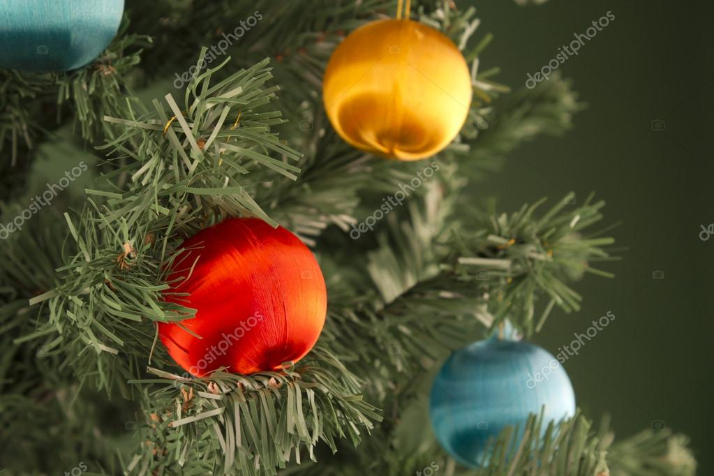 Several colored spheres hanging from a green Christmas tree. — Stock Photo #15374407
