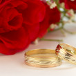 Wedding rings with red roses — Stock fotografie