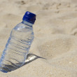 Stock Photo: Bottle of water on the sand