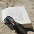 Close up of the sunglasses on a book — Stock Photo