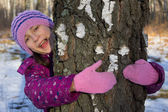 Happy small girl hug tree — Stock Photo