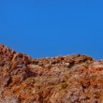 Red-grey-ochre-rocks-under-blue-sky — Stock Photo