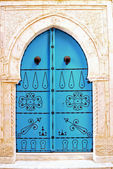 A-blue-door-with-black-studs-and-stone-ornament-at-doorway-in-Tu — Stock Photo