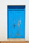 Blue-door-on-a-white-wall-doorway-with-wooden-grate-above — 图库照片