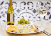 Sliced cheese with wine — Stock Photo