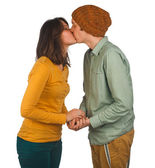 Beautiful young couple kissing against white background — Stock Photo