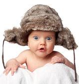 Sweet little baby in a huge fur hat — Stock Photo