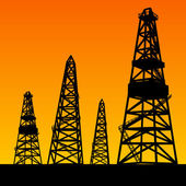 Oil rig silhouettes and orange sky — Stock Photo