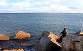 Man sitting on the big stone toward the sea. — Fotografia Stock