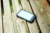 Mobile phone on the wooden chair — Stock Photo