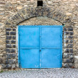 Stone wall with blue door — Stock Photo #24349411