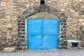 Stone wall with blue door — Stock Photo