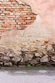Wall with chipped plaster, stone foundation and asphalt — Foto Stock