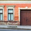 Facade of an old building with two windows and door — Stock Photo #25198591