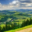 Panoramic view on village in hilly valley — Stock Photo #29248987