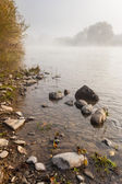Small boulders on foggy shore in autumn — Stock Photo