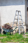 Metal ladder and a wheelbarrow by the old wall — Stock Photo