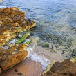 Seabed seen through clear waves crashing stones on shore — ストック写真