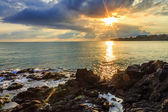 Menacing morning sea landscape with rocky coast and rising sun r — Stock Photo