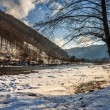 Slope to the river between the mountains in winter — Stock Photo