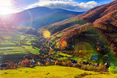 Light beam falls on hillside with autumn forest in mountain — Stock Photo