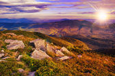 Light beam falls on rocky mountain with autumn forest — Stock Photo