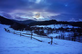 Fence by the road to snowy forest in the mountains — Stock Photo