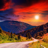 Mountain road near the coniferous forest with cloudy sunset sky — Stock Photo