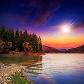 Autumn Mountain lake in coniferous forest at sunset — Photo