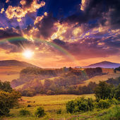 Cold fog on hot sunrise in mountains with rainbow — Stock Photo