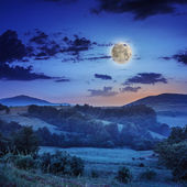 Niebla fría caliente amanecer en las montañas con la luna — Foto de Stock